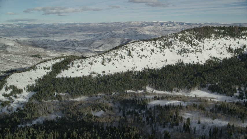 6K stock footage aerial video of snowy Wasatch Range mountain ridge encircled by evergreens in winter, Utah Aerial Stock Footage | AX126_281