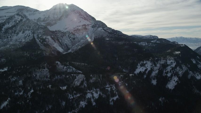 6K stock footage aerial video of sun over snowy Mount Timpanogos in wintertime, Utah Aerial Stock Footage | AX126_283