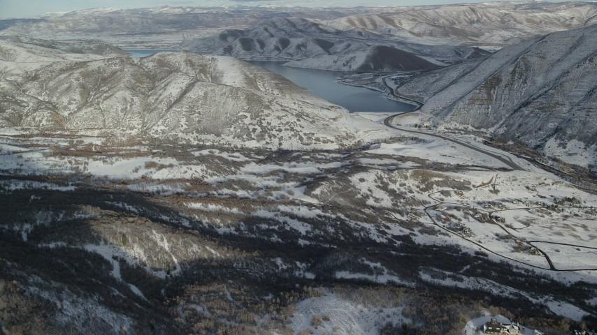 Approach Deer Creek Reservoir Beyond a Snowy Valley in Winter Aerial Stock Footage | AX126_301