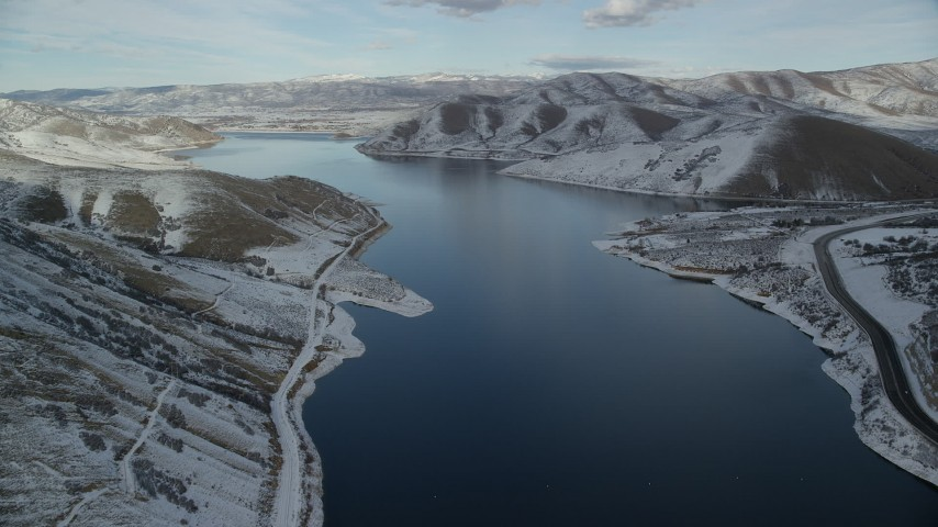 Fly Over Deer Creek Reservoir toward Heber City on the Distant Snowy Shore Aerial Stock Footage | AX126_307