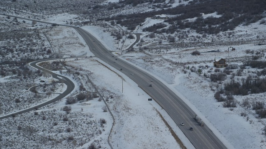 Orbit a Country Road through Winter Snow with Light Traffic Aerial Stock Footage | AX126_309