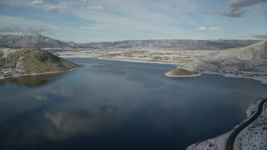 Approach Heber City on the Icy Shore of Deer Creek Reservoir in Winter Aerial Stock Footage | AX126_314