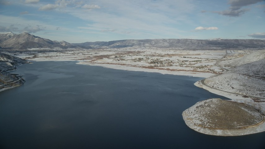 Approach Snowy Heber City from Icy Deer Creek Reservoir in Winter Aerial Stock Footage | AX126_316
