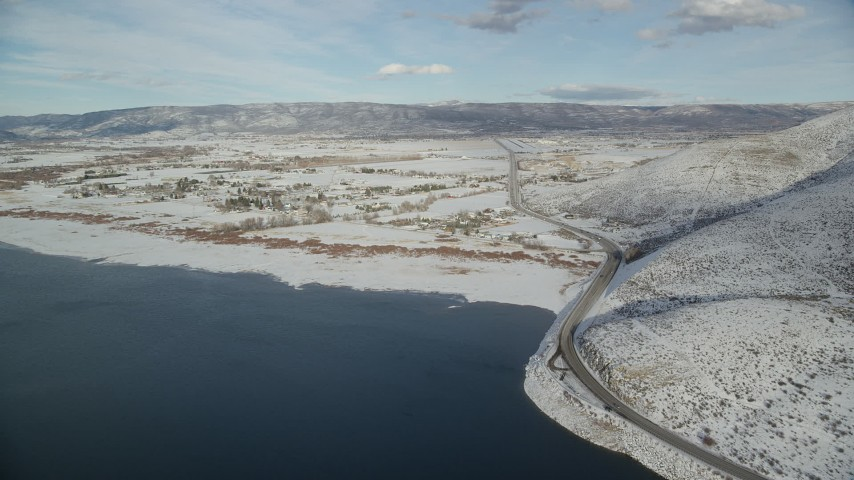 6K stock footage aerial video approach Heber City from reservoir, pan to highway with winter snow, Utah Aerial Stock Footage | AX126_317