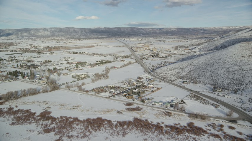 6K stock footage aerial video fly over homes in Heber City with winter snow near the highway, Utah Aerial Stock Footage | AX126_318