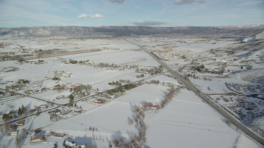 6K stock footage aerial video of rural Heber City homes with winter snow near the highway in winter, Utah Aerial Stock Footage | AX126_319