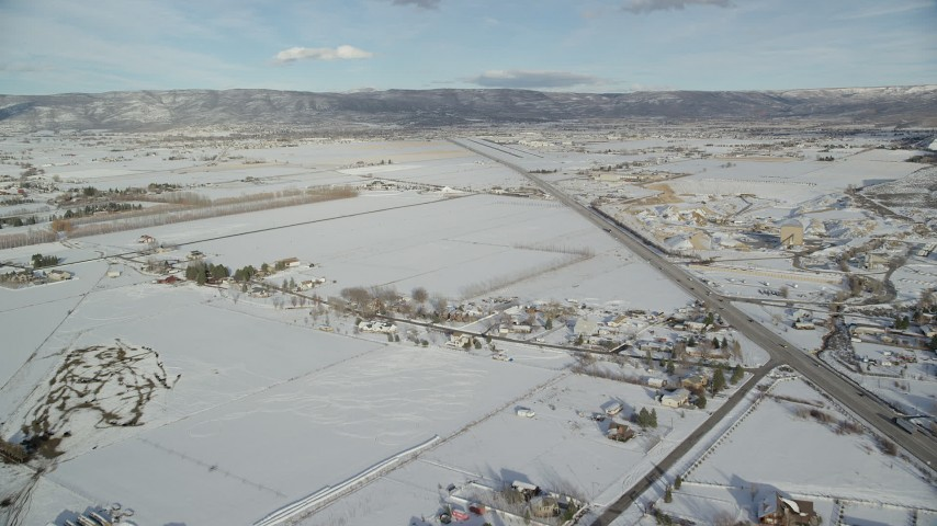 Fly Beside the Highway over Rural Homes with Winter Snow  Aerial Stock Footage | AX126_320