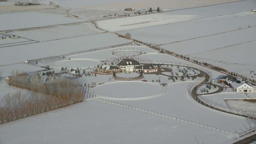 6K stock footage aerial video approach mansion surrounded by snowy fields in winter, Heber City, Utah Aerial Stock Footage | AX126_321