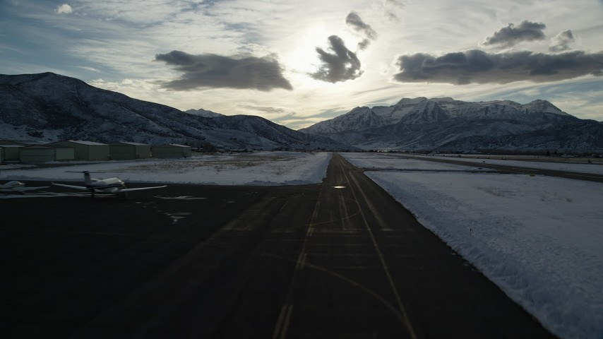 6K stock footage aerial video of lifting off from Heber City Municipal Airport with winter snow, Utah Aerial Stock Footage | AX127_001