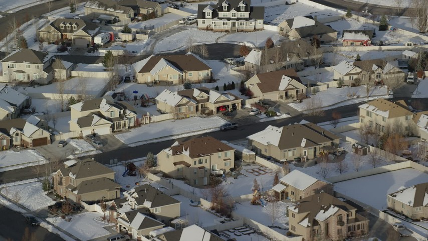 Tilt Down to Tract Homes in a Small Town Neighborhood with Winter Snow Aerial Stock Footage | AX127_004