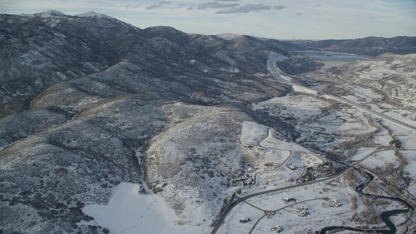 Fly Over Rural Homes and Approach Mountains with Light Snow in Utah Aerial Stock Footage | AX127_008