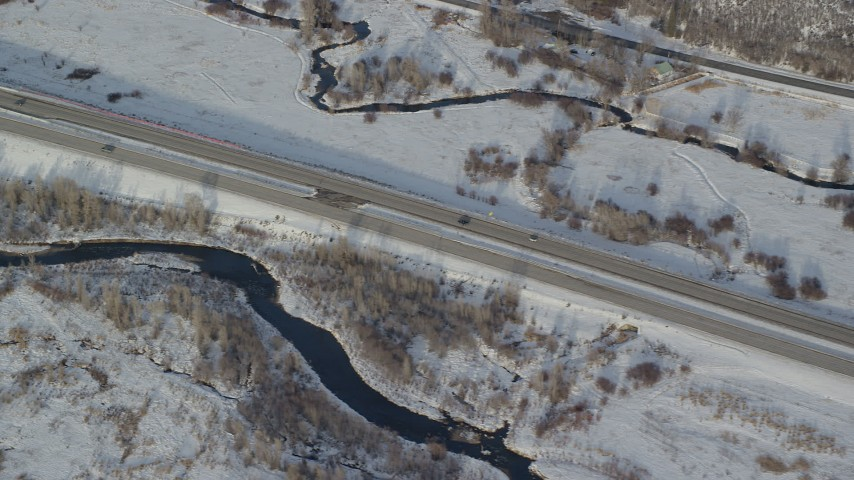 6K stock footage aerial video of tacking two cars on a highway through snowy fields in wintertime, Heber City, Utah Aerial Stock Footage | AX127_011