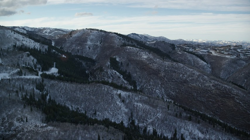 6K stock footage aerial video orbit mountains with light snow and leafless trees in wintertime, Utah's Wasatch Range at sunset Aerial Stock Footage | AX127_017