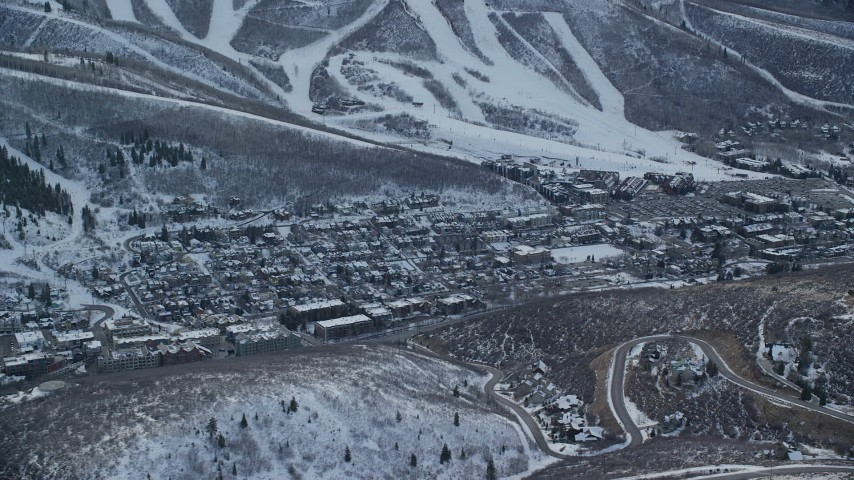 6K stock footage aerial video of passing by the center of town in Park City with winter snow on the ground at sunset, Utah Aerial Stock Footage AX127_022 | Axiom Images
