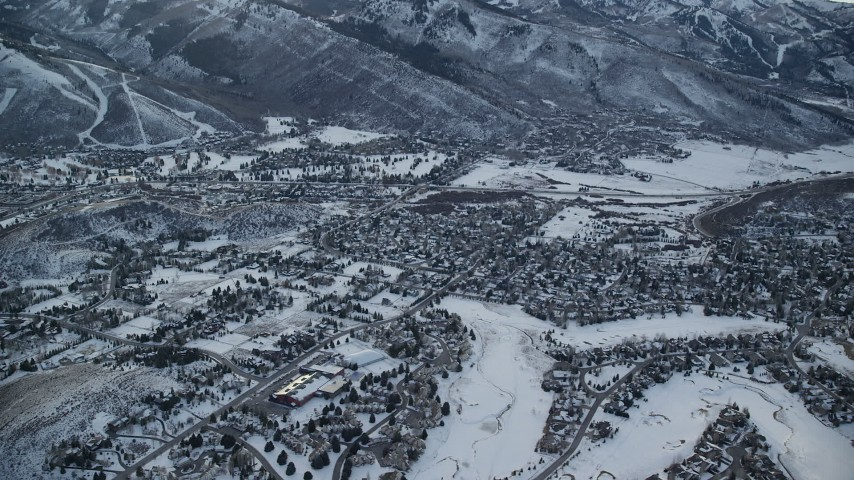 6K stock footage aerial video of flying by small town residential neighborhoods with winter snow at sunset, Park City, Utah Aerial Stock Footage | AX127_025