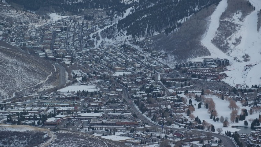 6K stock footage aerial video of Park City at sunset in the shadow of a snowy mountain in winter, Utah Aerial Stock Footage | AX127_029