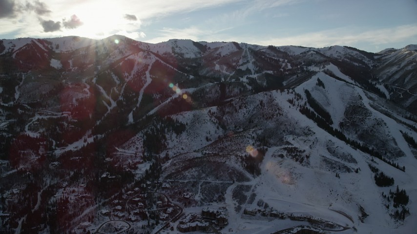 Orbit Snowy Mountains in Winter with the Sun Above Aerial Stock Footage | AX127_033