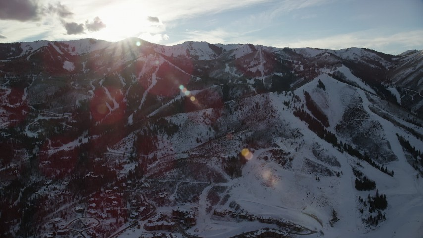 6K stock footage aerial video orbit snowy mountains in winter with the sun above, Wasatch Range, Utah Aerial Stock Footage | AX127_033