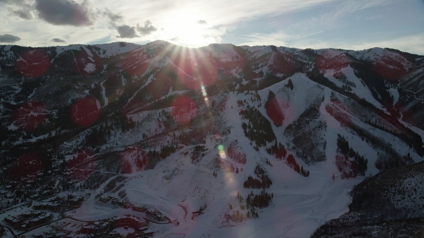 6K stock footage aerial video orbit Wasatch Range snow mountains with the sun over them, Utah Aerial Stock Footage | AX127_034