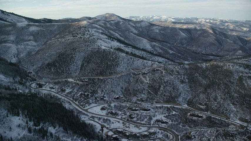 Fly Over Park City Mansions at the Base of a Snowy Mountain at Sunset Aerial Stock Footage   AX127_035