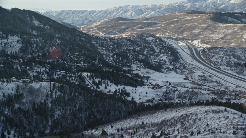 6K stock footage aerial video approach I-80 and homes on snowy mountain slopes at sunset in winter, Park City, Utah Aerial Stock Footage | AX127_041