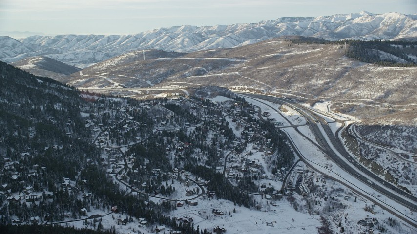 6K stock footage aerial video approach homes on a snowy slope by I-80 at sunset in winter, Park City, Utah Aerial Stock Footage | AX127_042