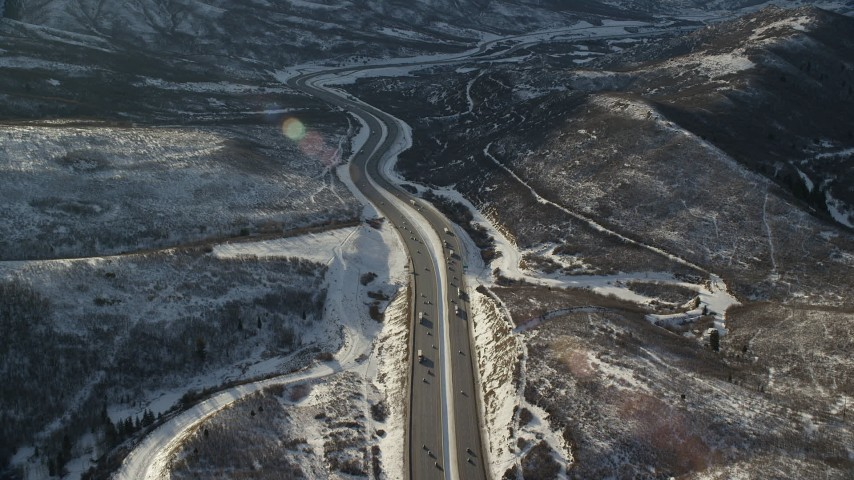 Fly Over Cars and Big Rigs on Interstate 80 through the Mountains in Winter at Sunset Aerial Stock Footage   AX127_047