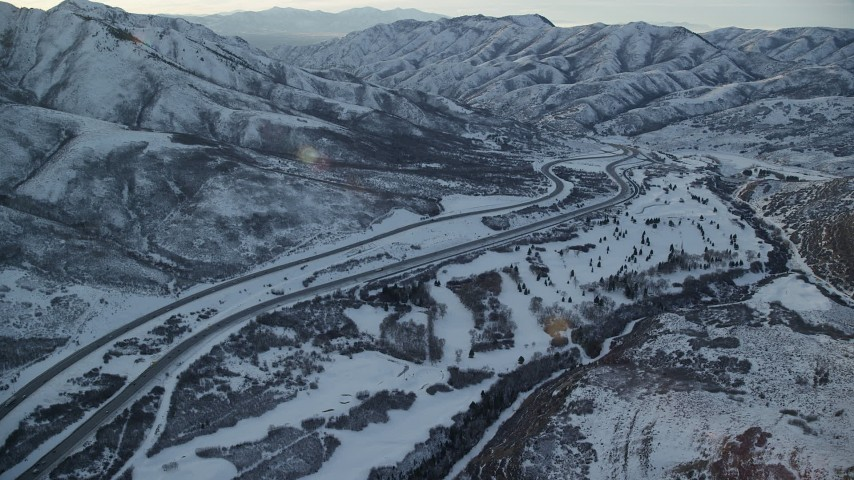 6K stock footage aerial video approach I-80 through the Wasatch Range with winter snow at sunset, Utah Aerial Stock Footage   AX127_052