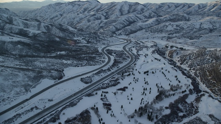 Approach Interstate 80 with Light Traffic through a Wintery Mountain Pass at Sunset Aerial Stock Footage | AX127_053