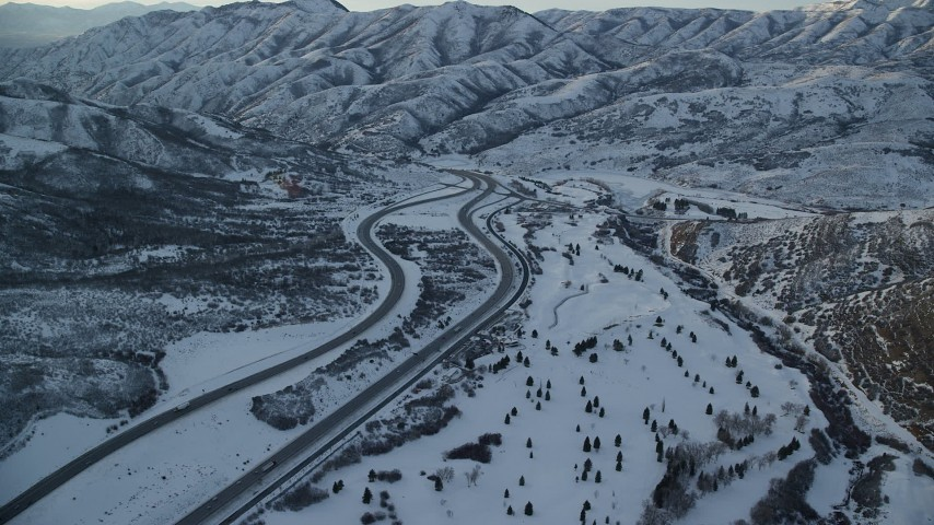 Approach an Interstate through Snowy Mountain Pass in Wintertime at Sunset Aerial Stock Footage   AX127_054