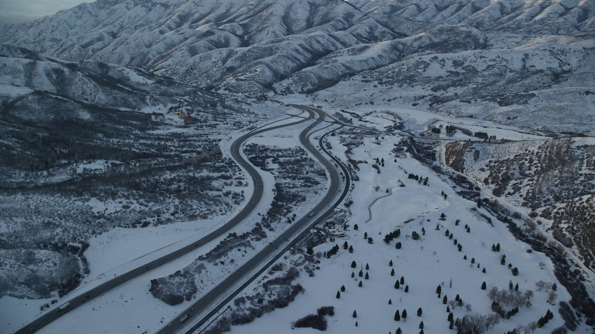 Approach an Interstate through Snowy Mountain Pass in Wintertime at Sunset Aerial Stock Footage | AX127_054