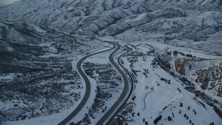 Fly Over a Freeway through Wintery Mountain Pass with Light Traffic at Sunset Aerial Stock Footage | AX127_055