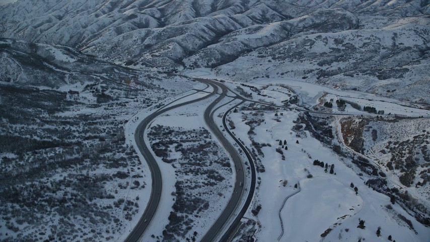6K aerial stock footage video of a freeway through wintery Wasatch Range pass with light traffic at sunset, Utah Aerial Stock Footage | AX127_055