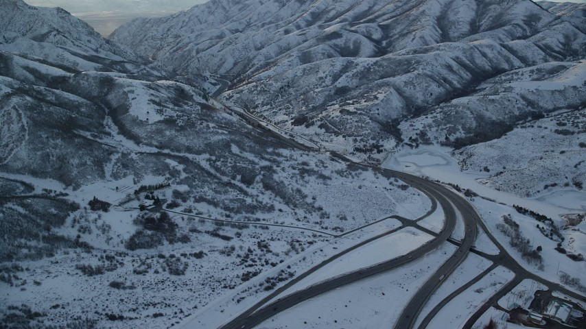 Follow Interstate 80 through Wasatch Range with Winter Snow at Sunset Aerial Stock Footage | AX127_056