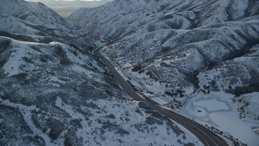 6K stock footage aerial video approach I-80 through a snowy mountain pass in wintertime at sunset, Wasatch Range, Utah Aerial Stock Footage | AX127_057