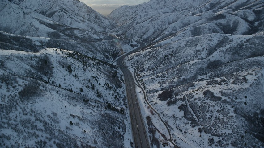 6K stock footage aerial video of I-80 through narrow mountain pass at sunset in winter, Wasatch Range, Utah Aerial Stock Footage | AX127_058