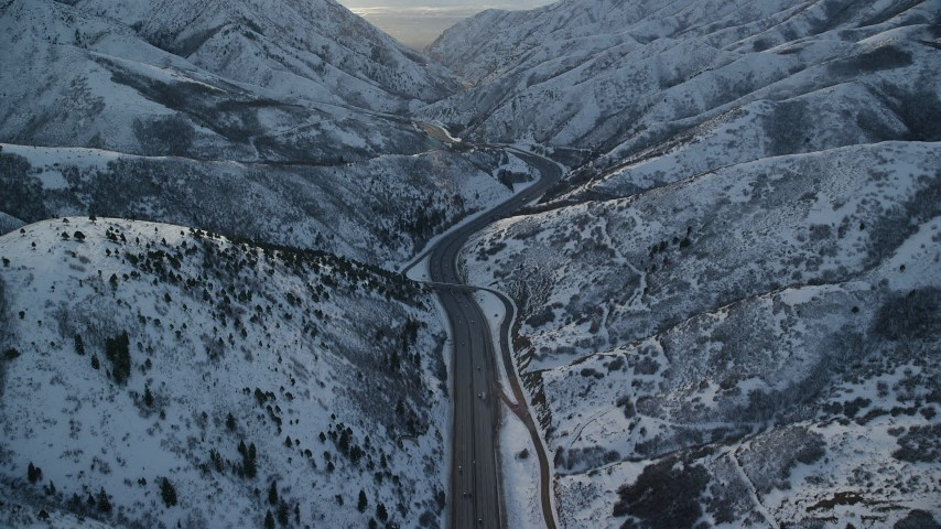 6K stock footage aerial video of I-80 curving through snowy Wasatch Range mountain pass at sunset, Utah Aerial Stock Footage | AX127_059