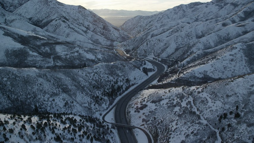 Approach a Curve in the Freeway Through a Snowy Mountain Pass at Sunset Aerial Stock Footage AX127_060