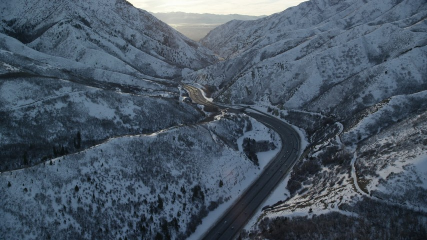 6K stock footage aerial video fly over a curve in wintery Wasatch Range mountain pass at sunset, Utah Aerial Stock Footage | AX127_061