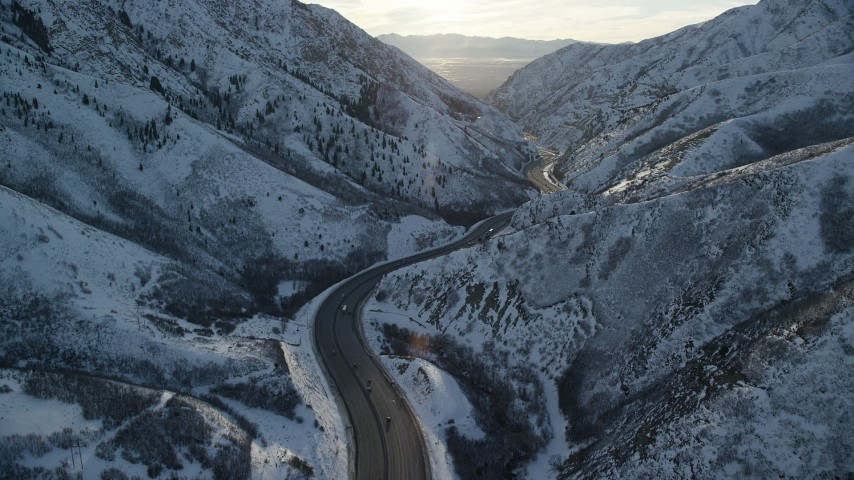 6K stock footage aerial video of interstate through Wasatch Range with winter snow at sunset, Utah Aerial Stock Footage | AX127_063
