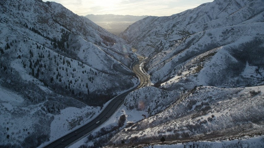 6K stock footage aerial video approach freeway through the Wasatch Range with winter snow at sunset, Utah Aerial Stock Footage | AX127_064