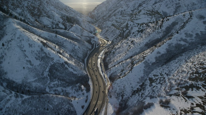 6K stock footage aerial video of traffic on I-80 through the snowy Wasatch Range at sunset, Utah Aerial Stock Footage | AX127_065