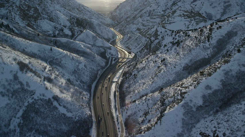Fly Over Freeway in the Wasatch Range with Winter Snow at Sunset Aerial Stock Footage   AX127_066