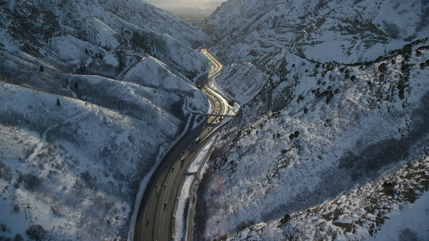 6K stock footage aerial video of freeway in the Wasatch Range with winter snow at sunset, Utah Aerial Stock Footage | AX127_066