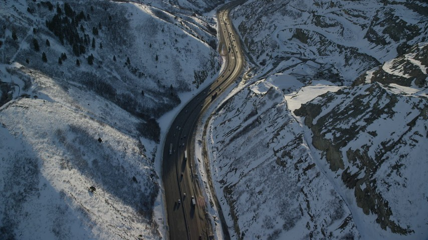 Fly Over Cars and Big Rigs Traveling through a Frozen Mountain Pass at Sunset Aerial Stock Footage   AX127_068