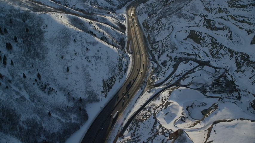 6K stock footage aerial video of cars and big rigs traveling through a frozen mountain pass at sunset, Wasatch Range, Utah Aerial Stock Footage | AX127_068