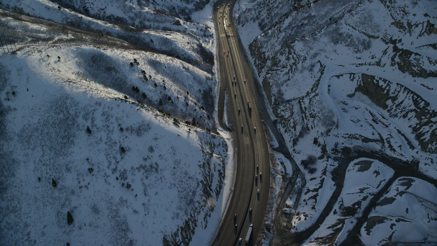 Fly Over a Big Rig and Cars Traveling the Snowy Mountain Pass at Sunset Aerial Stock Footage | AX127_069