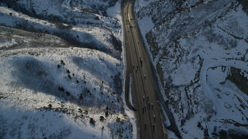 Fly Over a Big Rig and Cars Traveling the Snowy Mountain Pass at Sunset Aerial Stock Footage AX127_069