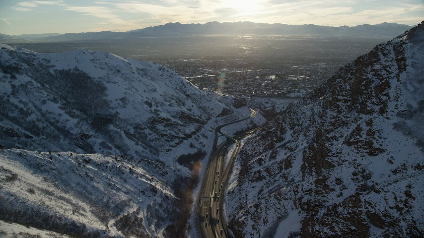 6K stock footage aerial video of I-80 through wintery Wasatch Range mountain pass toward Salt Lake City at sunset, Utah Aerial Stock Footage | AX127_071