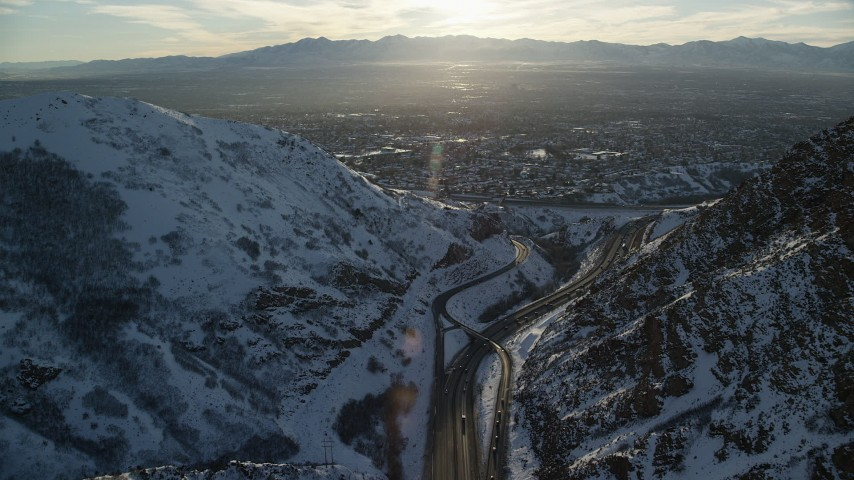 Approach Salt Lake City Suburbs from Interstate 80 through Wasatch Range at Sunset Aerial Stock Footage | AX127_072